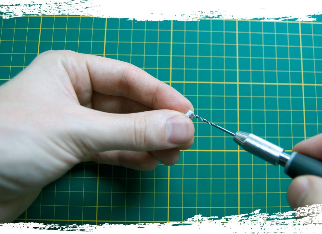 Step 2: Use a hobby drill to carefully drill some holes through the hands. I used a drill bit that is roughly the same size as the piece of plastic rod.