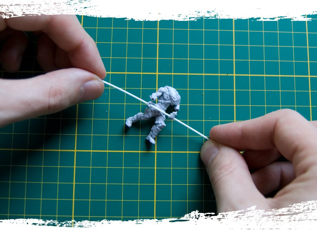 Step 5: Put the piece of plastic rod through the hands of the model, make sure the hands are facing the right way and are on the right side. Now you can glue the hands to the arms using some super glue.